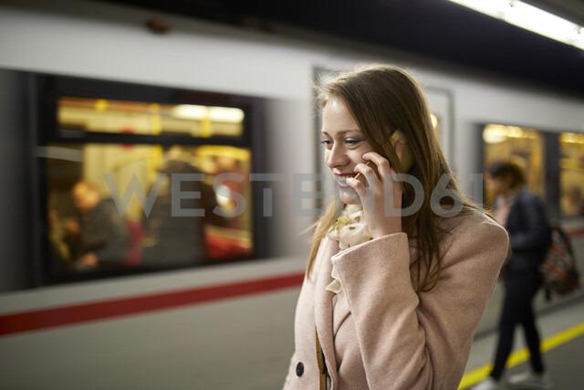 Austria, Vienna, smiling young woman on the phone at underground station platform - ZEDF01946 - Zeljko Dangubic/Westend61