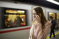 Austria, Vienna, smiling young woman on the phone at underground station platform - ZEDF01946