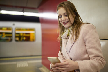 Austria, Vienna, portrait of smiling young woman at underground station  looking at smartphone - ZEDF01949