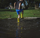 Rear view of playful boy stamping Foot while standing in puddle at park - CAVF61993