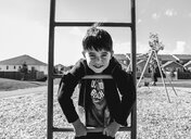 Portrait of cute boy leaning on steps at playground during summer - CAVF61996