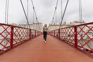 Confident woman walking on Paul-Couturier Footbridge over Saone River against buildings in city - CAVF62026