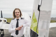 Portrait of confident male pilot standing by airplane against cloudy sky on airport runway - CAVF62053