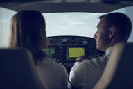 Rear view of pilot giving training to male trainee in flight simulator - CAVF62059