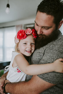 Portrait of happy cute daughter embracing father at home - CAVF62065
