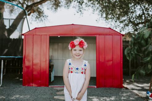Portrait of cute smiling girl wearing tiara standing against red garage in yard - CAVF62068