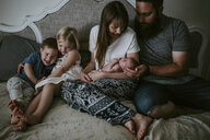 Family with newborn baby girl sitting on bed at home - CAVF62074