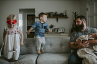 Father carrying newborn daughter looking at children playing on sofa in living room - CAVF62077