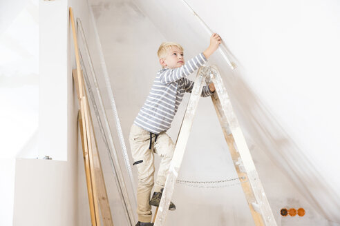 Boy with pocket rule on ladder measuring wall in attic to be renovated - MFRF01169