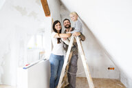 Portrait of happy family working on loft conversion - MFRF01178