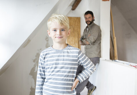 Portrait of confident boy working with father on loft conversion - MFRF01181