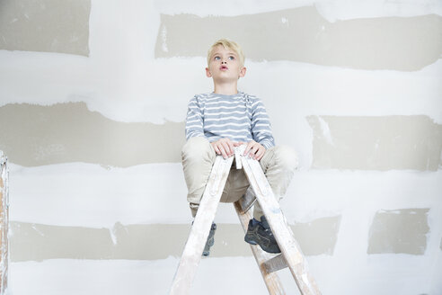 Boy sitting on ladder in attic to be renovated - MFRF01187