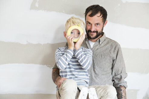 Portrait of father and son with sticky tape working on loft conversion - MFRF01190