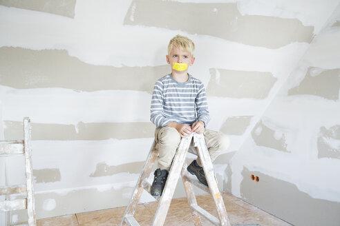 Deutschland, NRW, Haus, Baustelle, Dach, Dachboden, Holz, Dachausbau, Dachschraege, Portrait, Junge sitzt auf Leiter mit einem Stueck Klebeband auf dem Mund und schaut zornig - MFRF01193