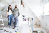 Portrait of confident couple standing in attic to be renovated - MFRF01199