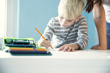 Boy doing homework with mother leaning on desk - MFRF01211