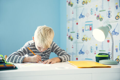 Focused boy doing homework at desk in children's room - MFRF01217