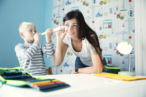 Mother and son having fun at desk in children's room - MFRF01223