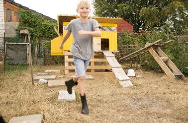 Portrait of happy boy running at chickenhouse in garden - MFRF01247
