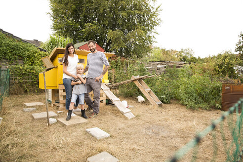 Portrait of confident family with Polish chicken at chickenhouse in garden - MFRF01256