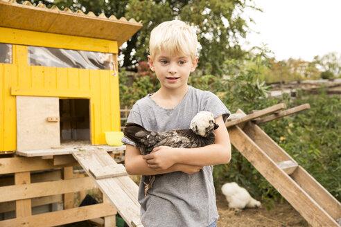 Deutschland, NRW, Garten, Huehnerstall, Huehner, Hollaender Haubenhuhn, Portrait, Junge haelt Huhn auf dem Arm - MFRF01259