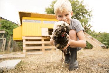 Boy holding Polish chicken at chickenhouse in garden - MFRF01262