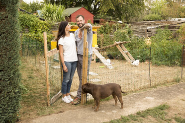 Portrait of couple with dog standing at chickenhouse in garden - MFRF01265