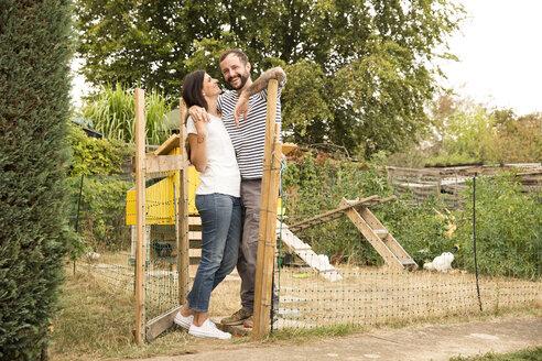Deutschland, NRW, Garten, Huehnerstall, Huehner, Portrait, Mann und Frau stehen Arm in Arm an Zaun - MFRF01268