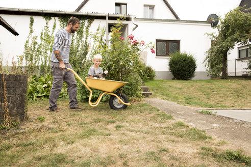 Deutschland, NRW, Garten, Haus, Portrait,  Junge sitzt mit Hollaender Haubenhuhn in Schubkarre und wird von Vater geschoben - MFRF01274