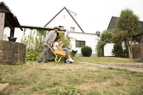 Deutschland, NRW, Garten, Haus, Portrait, Frau und Junge sitzten in Schubkarre und werden von Mann geschoben - MFRF01277