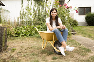 Portrait of smiling woman sitting in wheelbarrow in garden - MFRF01280