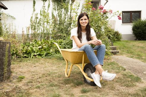 Deutschland, NRW, Garten, Portrait, Frau sitzt in Schubkarre, Portrait - MFRF01280