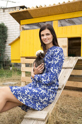 Portrait of smiling woman with Polish chicken at chickenhouse in garden - MFRF01283