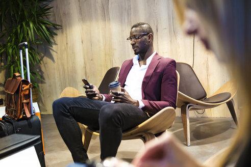 Businessman with luggage sitting in hotel lobby, using smartphone, drinking coffee - JSRF00163