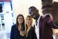 Business people taking a selfie in a hotel lobby - JSRF00172
