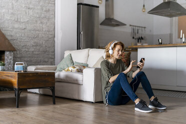 Young woman sitting on floor at home, using smartphone, wearing headphones - AFVF02532