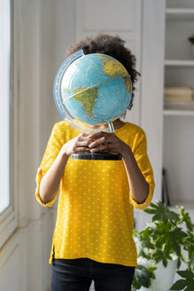 Woman holding globe, hiding face - AFVF02544