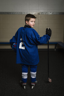 Portrait serious boy ice hockey player in uniform holding hockey stick and helmet - HEROF26274