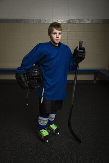 Portrait serious boy ice hockey player in uniform holding hockey stick and helmet - HEROF26277