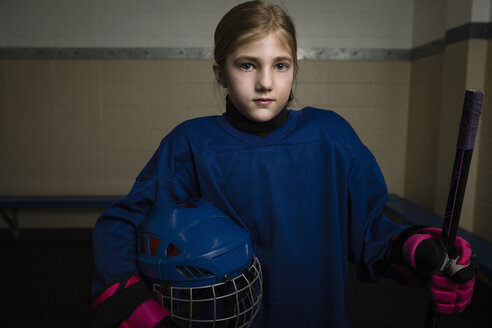 Portrait serious girl ice hockey player in uniform holding hockey stick and helmet - HEROF26280