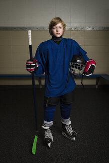 Portrait serious boy ice hockey player in uniform holding hockey stick and helmet - HEROF26286
