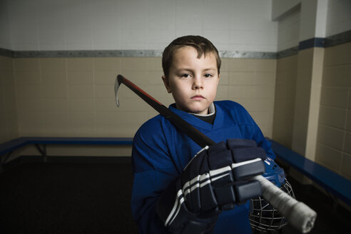 Portrait serious boy ice hockey player in uniform holding hockey stick and helmet - HEROF26289