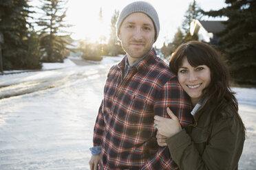Portrait smiling couple hugging on snowy road - HEROF26298