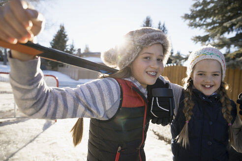 Portrait smiling girls playing ice hockey in sunny driveway - HEROF26310