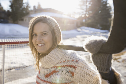 Portrait smiling blonde woman playing ice hockey in sunny, snowy driveway - HEROF26313