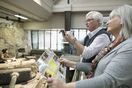 Senior couple with smart phone and brochure photographing exhibit in war museum - HEROF26358