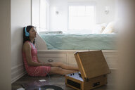 Serene teenage girl listening to music records with headphones in bedroom - HEROF26412