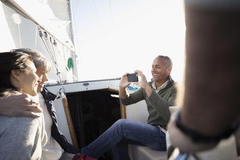 Senior man with camera phone photographing women on sailboat - HEROF26439