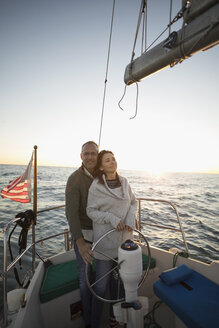 Serene affectionate couple at helm of sunset sailboat - HEROF26451