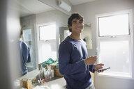 Portrait smiling man brushing teeth and using smart phone in bathroom - HEROF26466